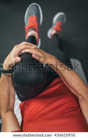 healthy man stretching leg before gym workout. Fitness strong male athlete on floor mat and towel warming up with bottle and cellphone. - stock photo
