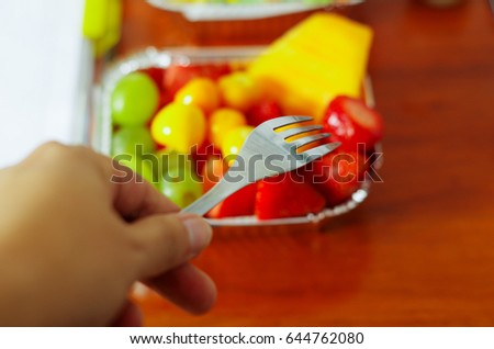 Healthy man using a fork to eat in the office a delicious fresh fruit salad on aluminium box on wooden table above view