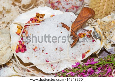 Healthy marine bath salts rich in minerals mixed with dried aromatic rose petals for a luxury bath treatment at a spa - stock photo