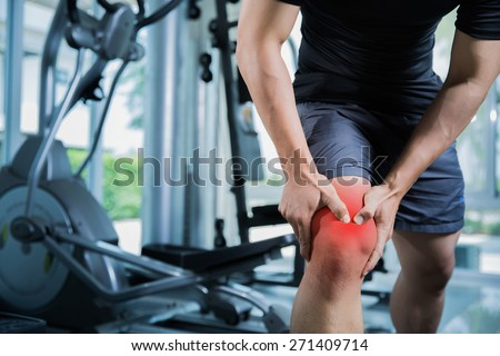 Healthy men Injury from exercise in the gym, he injured his knee - stock photo