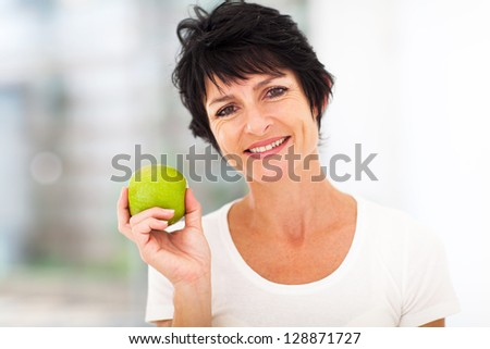 healthy mid age woman holding apple closeup