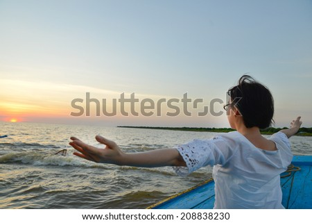 Healthy middle aged woman doing fitness stretching by wood boat at sunset - stock photo
