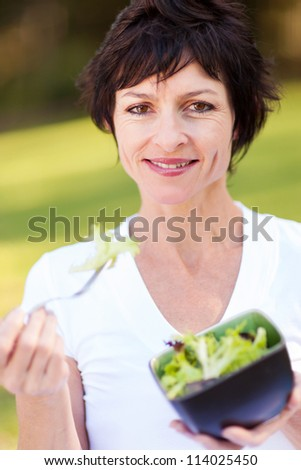 healthy middle aged woman eating bowl of salad - stock photo