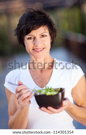 healthy middle aged woman eating green salad - stock photo