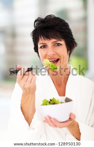 healthy middle aged woman eating green salad