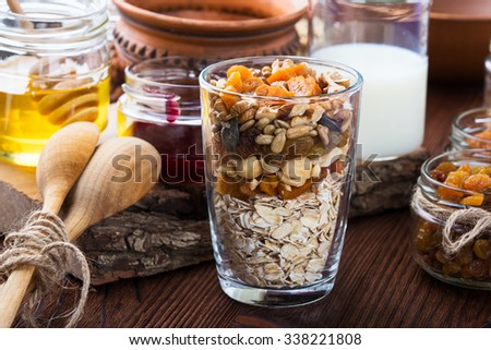 Healthy morning muesli ingredients in glass cup. Raw rolled oats, dried fruits, seeds, honey, nuts and milk on rustic wooden board - stock photo