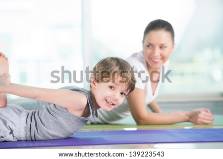 Healthy morning stretching - woman with son doing gymnastic exercise at home