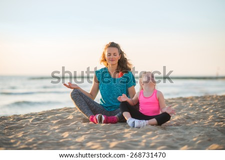 Healthy mother and baby girl doing yoga on beach in the evening - stock photo