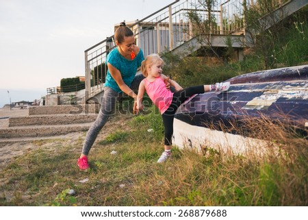 Healthy mother and baby girl stretching outdoors