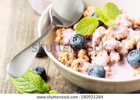 Healthy muesli with blueberry and mint in bowl on wooden table - stock photo