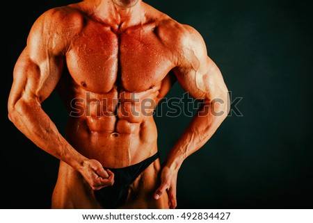 Healthy muscular body bodybuilder on a black background