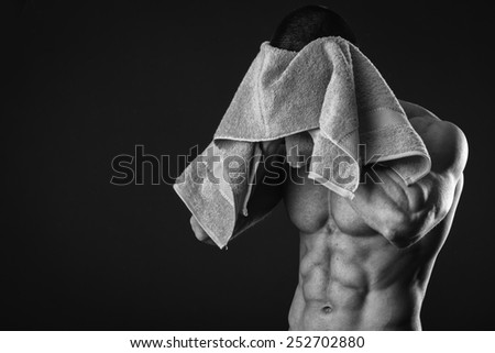 Healthy muscular young man after a workout on dark background.Fitness man holding a green towel against dark background.Strong Athletic Man Fitness Model Torso showing  abs. holding towel. - stock photo