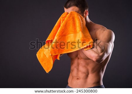 Healthy muscular young man after a workout on dark background.Fitness man holding a orange towel against dark background.Strong Athletic Man Fitness Model Torso showing  abs. holding towel. - stock photo