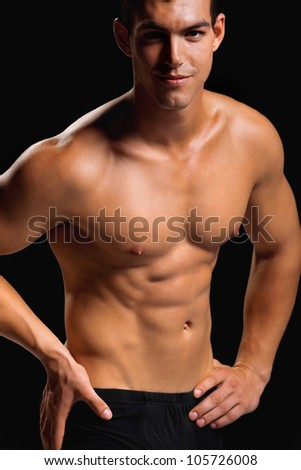 Healthy muscular young man. Isolated on black background.  Shallow DoF with focus on chest. - stock photo