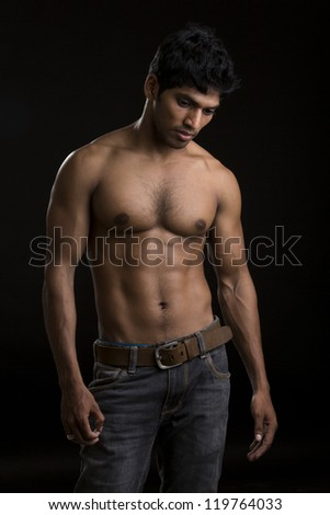 Healthy muscular young man on dark background.
