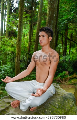 Healthy muscular young man sitting doing yoga over forest,