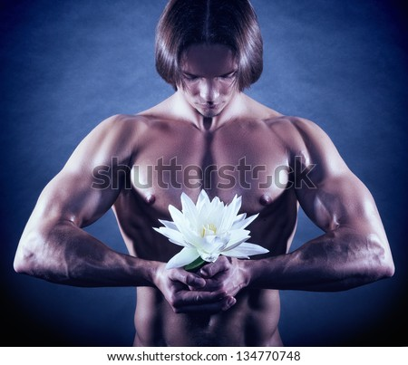 Healthy muscular young man with white lotus on dark background - stock photo