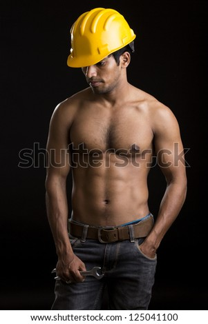 Healthy muscular young man with yellow helmet on black.