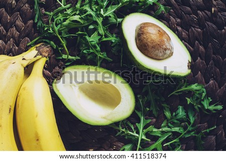 Healthy natural organic food background. Bananas, avocado and arugula leaves, top view. Fresh ingredients for a green smoothie, vegan vitamin detox drink - stock photo