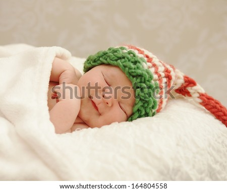 Healthy newborn baby smiling in sleep wearing a Christmas elf hat - stock photo