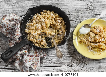 Healthy oat apple crumble in a frying pan on rustic light wood background - stock photo