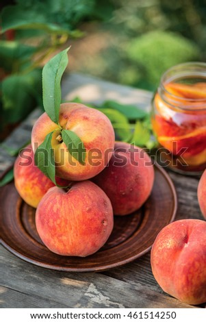 Healthy organic food, healthy fruits peaches. Ripe and tasty and juicy peaches lie on a plate on a wooden table in the orchard. Large peaches were ripped straight from the tree. Sliced peach in Jar.