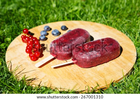 Healthy organic food: Homemade ice cream pops with yoghurt and different berries: red currant, blueberry, strawberry and blackberry - stock photo