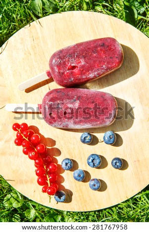 Healthy organic food: Homemade ice cream pops with yoghurt and different berries: red currant, blueberry, strawberry and blackberry. Vegan sweet food. - stock photo