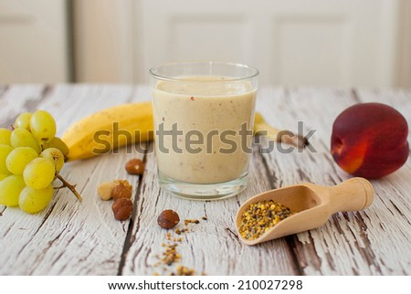 healthy organic fruit and nuts smoothie on wooden board - stock photo