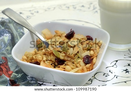 Healthy organic homemade granola in a bowl on an ornate serving tray with a glass of milk and a napkin - stock photo