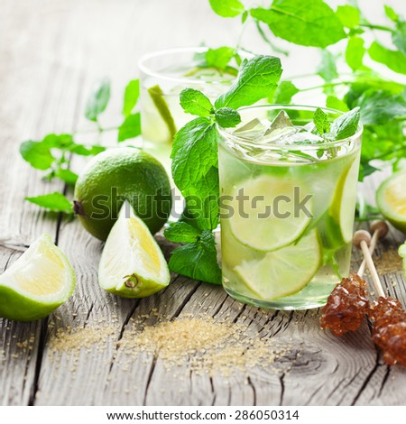 Healthy organic lemonade with fresh lemon, lime and mint on rustic wooden background, selective focus