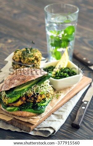 Healthy organic meal: Vegan sourdough burger with sprouted greens and chickpea rissole - stock photo
