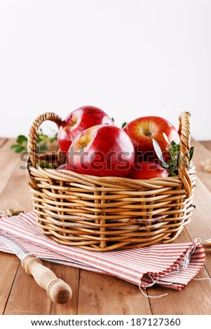 Healthy organic red apples in a straw basket  on a wooden background - stock photo