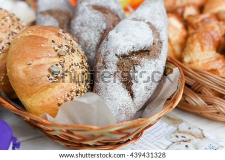 Healthy organic rye and white wheat homemade bread loafs with sesame in basket outdoors for sale. Country fair, tasty fresh bread loafs. Crispy buns. Whole grain bread - stock photo