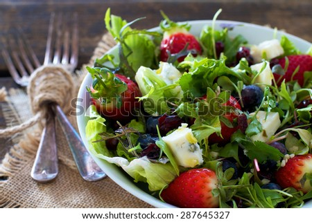 Healthy organic salad greens with berries and cheese on a natural background of burlap and wood