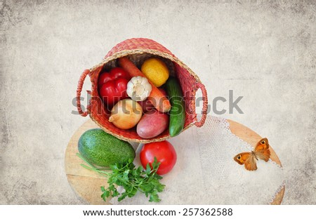 Healthy organic vegetables for cooking in basket on the cutting board and butterfly. Image done on old paper texture in decorative retro style. Healthy food still life for kitchen interior - stock photo