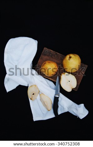 Healthy organic yellow pears on the desk. Fruit background. Ripe fresh organic  pears on black  background. Pear autumn harvest. Sliced pear on a chopping board. Top view.  Autumn harvest. Knife.  - stock photo