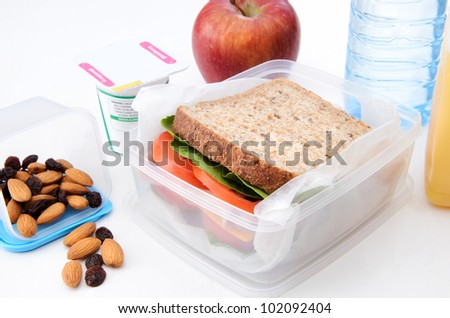 Healthy packed lunch with wholemeal sandwich, apple, dried fruit, nuts and yoghurt isolated on white - stock photo