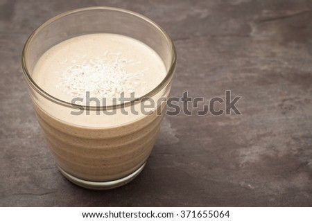 Healthy peanut butter banana smoothie milkshake topped with coconut. Served on a gray stone slate background. - stock photo