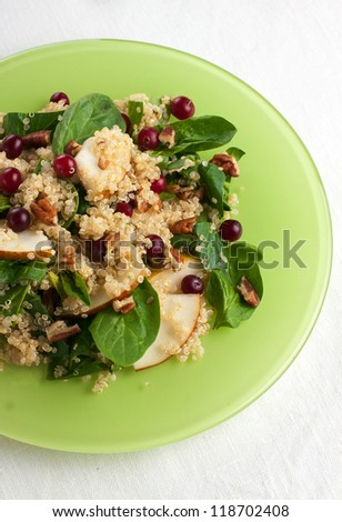 Healthy pear quinoa salad with nuts and berries shoot from above - stock photo