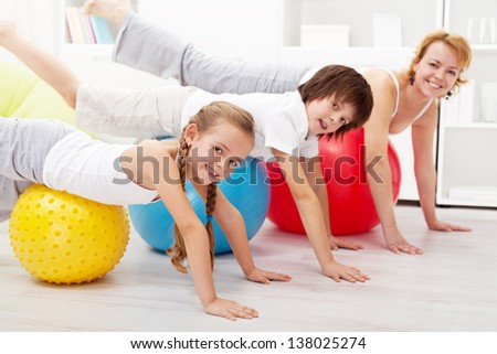 Healthy people doing balancing exercise at home on large gymnastic balls