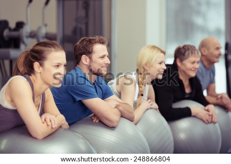 Healthy People Exercising Using Big Balls for Stability at the Fitness Gym. - stock photo