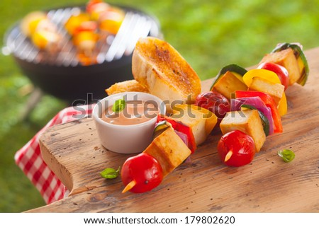 Healthy picnic lunch at a summer barbecue with grilled smoked Tofu and vegetable kebabs served with a savory sauce and toasted baguette on a wooden table - stock photo