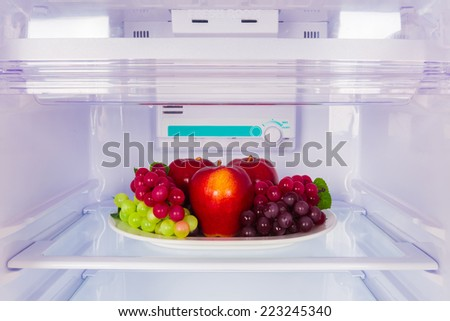 healthy plate of fruits in the refrigerator  - stock photo