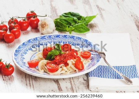 Healthy plate of Italian spaghetti topped with a tasty tomato and fresh basil on a rustic white wooden table - stock photo