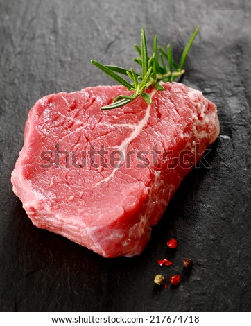 Healthy portion of lean uncooked beef steak garnished with a sprig of fresh rosemary lying on a dark surface with whole peppercorns for seasoning - stock photo