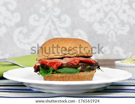 Healthy portobello mushroom burger on a whole wheat roll with roasted peppers, provolone cheese and greens.  A side bowl of pesto mayonnaise.  - stock photo