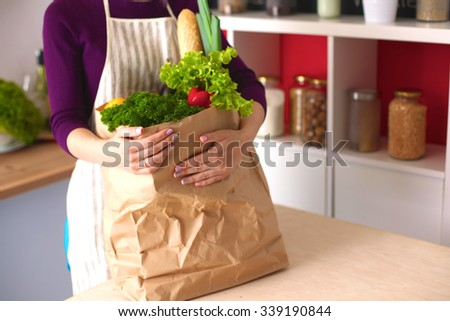 Healthy positive happy woman holding a paper shopping bag full of fruit and vegetables - stock photo