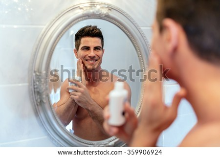 Healthy positive male treating skiing with lotion after shaving - stock photo