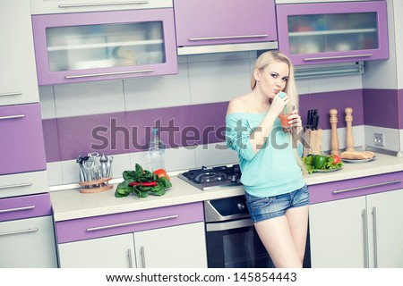 Healthy pregnancy concept. Portrait of a lovely young pregnant woman drinking fresh orange juice through sipper in her modern hi-tech kitchen. Trendy clothing on girl. Copy-space. Indoor shot